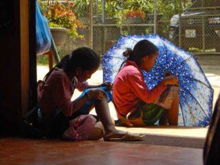 Bambine vietnamite ricamano all'ombra di un ombrello